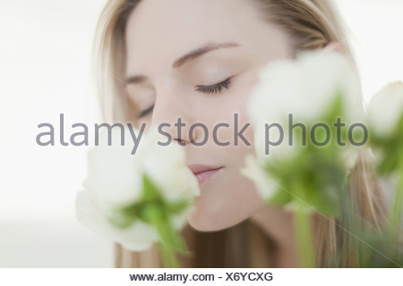 Close up of woman smelling flowers - Stock Photo