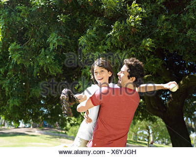 Father picking up and embracing son 10 12 in park boy holding baseball bat and glove smiling - Stock Photo