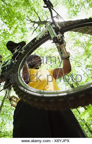 Male cyclist carrying bike in forest - Stock Photo