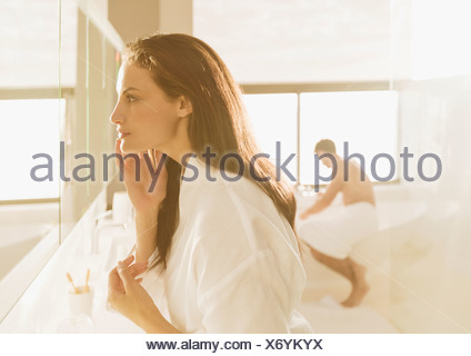 Woman looking at face in mirror - Stock Photo