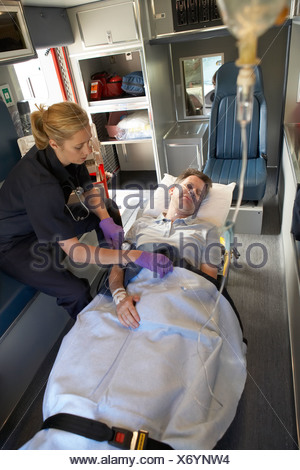 Paramedic with patient in ambulance - Stock Photo