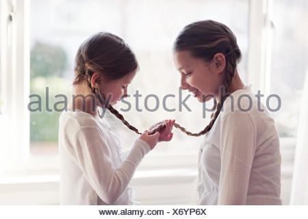 Two girls with their plaits tied together - Stock Photo