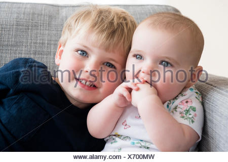 Boy (2-3) with baby sister (12-17 months) sitting on sofa - Stock Photo