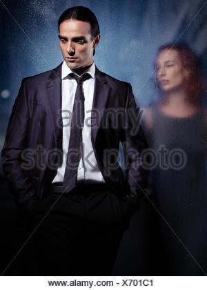 Man in a suit walking away leaving a woman behind wet glass door - Stock Photo
