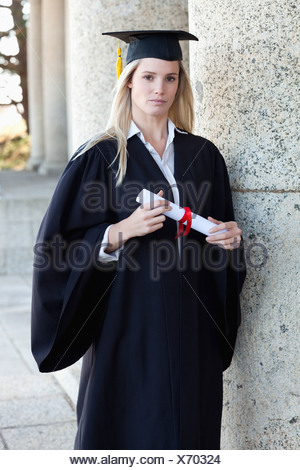 Young serious graduating student holding her diploma - Stock Photo