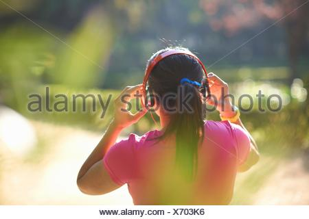 Rear view of mature woman with pony tail wearing headphones - Stock Photo