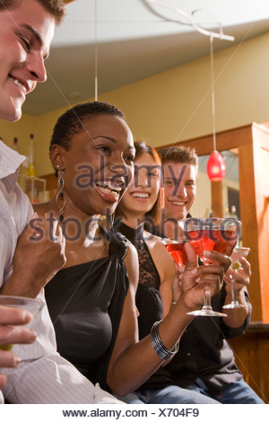 Young adult friends holding drinks and sitting together at bar - Stock Photo