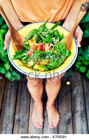 Sweden, Uppland, Danderyd, Young woman holding plate with salad - Stock Photo
