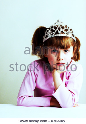 A girl wearing a pink top and tiara - Stock Photo