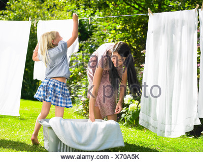 Mother and daughter doing the laundry - Stock Photo