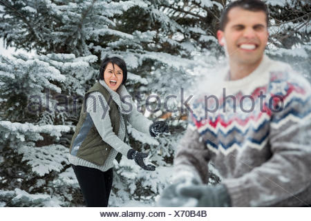 Couple having a snowball fight - Stock Photo