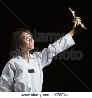 Young woman lifting a trophy and smiling - Stock Photo