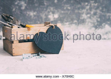 Wooden box with carpenters tools and a heart shape - Stock Photo