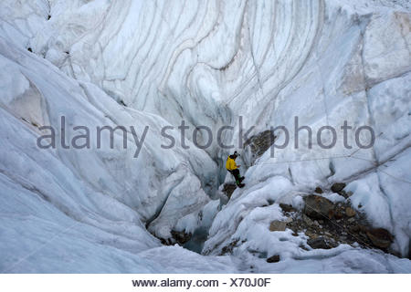 Italian cave explorer and Rolex Award 2014 winner Francesco Sauro rigs the ropes and begins his descent down into a large moulin. - Stock Photo