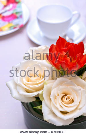 Kaffeegedeck aus weißem Porzellan mit Blumenarrangement aus weißen Rosen - Stock Photo