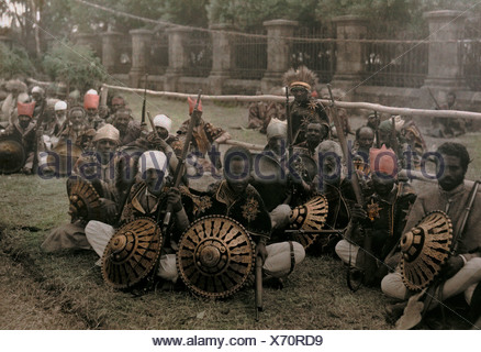 Soldiers pose with their weaponry during a coronation ceremony. - Stock Photo