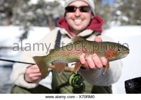 A man out fly fishing on a winter day. - Stock Photo