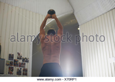 Man lifting kettlebell in gym - Stock Photo