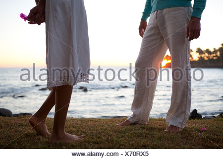 A man talks with a shy woman near the ocean at sunset. - Stock Photo