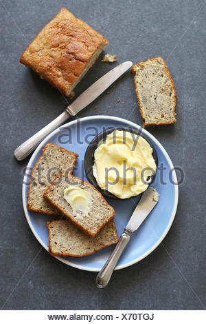 Slices of banana  bread on plate and butter on plate - Stock Photo