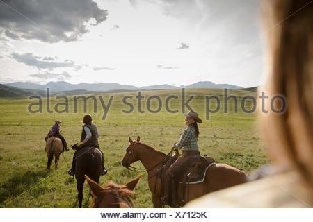Female ranchers horseback riding in sunny remote field - Stock Photo