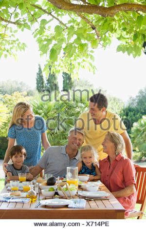 Multi-generation family having breakfast outdoors - Stock Photo