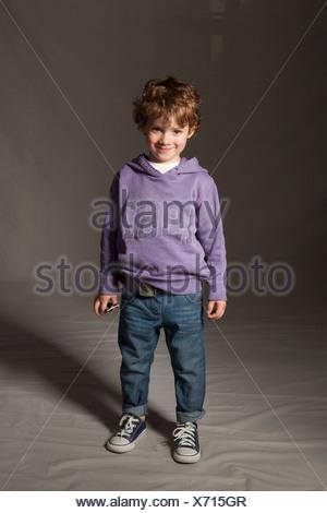 Boy smiling in studio - Stock Photo