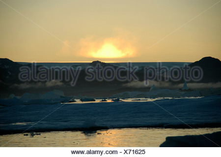 Evening red above mountains with snow mist water with ice-pack Eastgreenland - Stock Photo