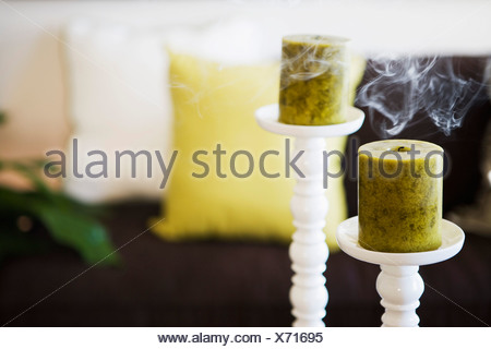 Two Unlit Candles with Smoke on Tall Candlesticks - Stock Photo