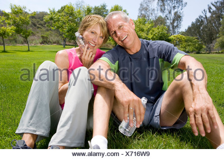 Mature couple sitting in park with water bottles, smiling, portrait - Stock Photo