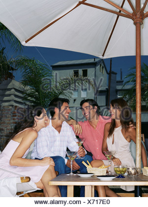 Friends having a drink under a parasol - Stock Photo