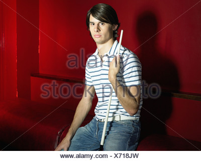 One man sitting in a bar holding pool cue - Stock Photo