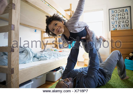 Father lifting flying daughter in bedroom - Stock Photo