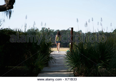 A woman walking up a wooden walkway, rear view - Stock Photo