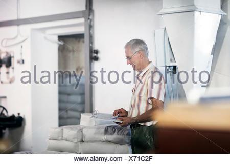Male miller stock taking sacks of flour at wheat mill - Stock Photo