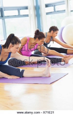 Fit class stretching legs on mats at yoga class - Stock Photo