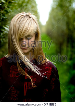 Sad woman in forest - Stock Photo