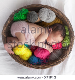 Cute newborn baby girl sleeping with ball of wools in basket, Fürstenfeldbruck, Bavaria, Germany - Stock Photo