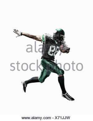 Studio shot of male football player running with ball - Stock Photo