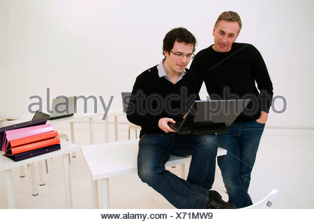 Two relaxed business men look at laptop - Stock Photo