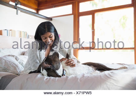Smiling woman petting dog on bed - Stock Photo