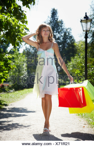 Young woman wearing a summer dress, holding shopping bags while running happily through a park - Stock Photo