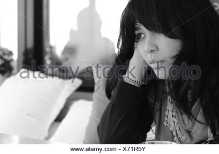 Portrait of woman sitting on a couch - Stock Photo