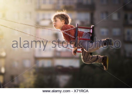Boy on a swing in playground - Stock Photo