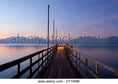 Jetty in Seebruck on Chiemsee lake overlooking the Chiemgau Alps at dusk, Bavarian Alps, Bavaria, Germany, Europe, PublicGround - Stock Photo