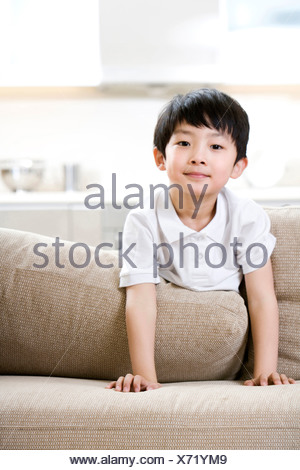 Little boy playing on the sofa - Stock Photo