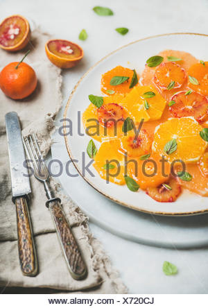 Fresh mixed citrus fruit salad with mint and honey on white ceramic plate over grey background, selective focus. Vegan, vegetarian, healthy, dieting,  - Stock Photo