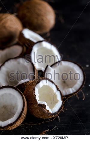 Fresh cracked coconuts are displayed on a dark background - Stock Photo