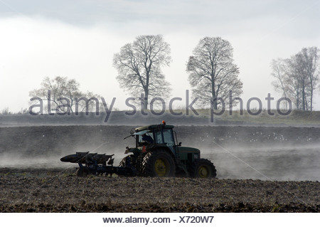 Side view of a tractor plowing in foggy field in autumn - Stock Photo