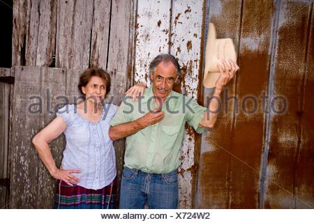 Portrait of senior couple standing near weathered barn wall - Stock Photo
